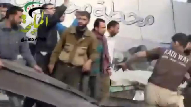 This citizen journalism image taken from video provided by Shaam News Network, which has been authenticated based on its contents and other AP reporting, shows people gathered at the site of a Syrian government airstrike on a gas station in the eastern Damascus suburb of Mleiha, Syria, Wednesday, Jan. 2, 2013. Activists say dozens of people have been killed or wounded in an air raid on a gas station near the capital Damascus. (AP Photo/Shaam News Network via AP video)