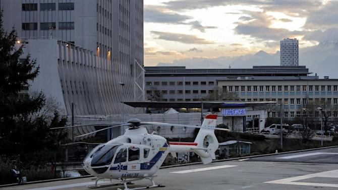 """An helicopter is seen in front of the Grenoble hospital, in the French Alps, where former seven-time Formula One champion Michael Schumacher is treated after he sustained a head injury during a ski accident in Meribel France, Sunday, Dec. 29, 2013. The French Mountain Gendarmerie said Schumacher was wearing a helmet when he had a hard fall at Meribel and that he sustained a """"relatively serious"""" head injury. He was initially taken to a local hospital and later transferred to a hospital in the city of Grenoble. (AP Photo/Laurent Cipriani)"""