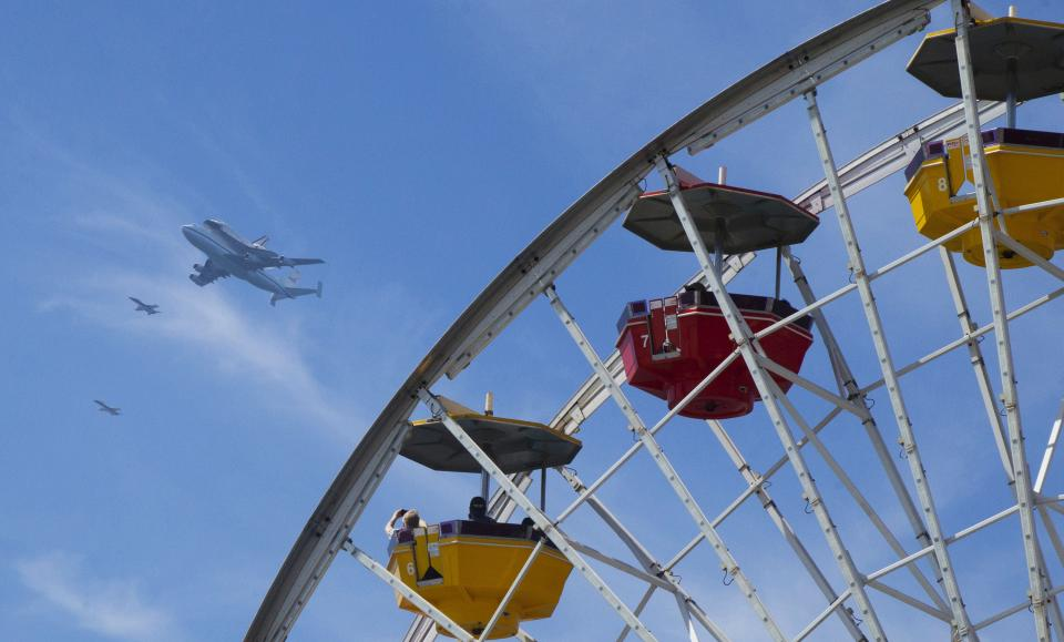 This image provided by Pacific Park shows the Space Shuttle Endeavour atop a modified 747 passing over the Santa Monica Pier Friday Sept. 21, 2012 in Santa Monica, Calif. The pier offered free ferris wheel rides during the flyover of the shuttle.  (AP Photo/Pacific Park, Brandon Wise)