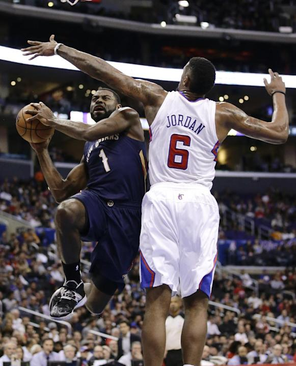 New Orleans Pelicans' Tyreke Evans, left, drives to the basket against Los Angeles Clippers' DeAndre Jordan during the first half of an NBA basketball game Wednesday, Dec. 18, 2013, in Los Ang