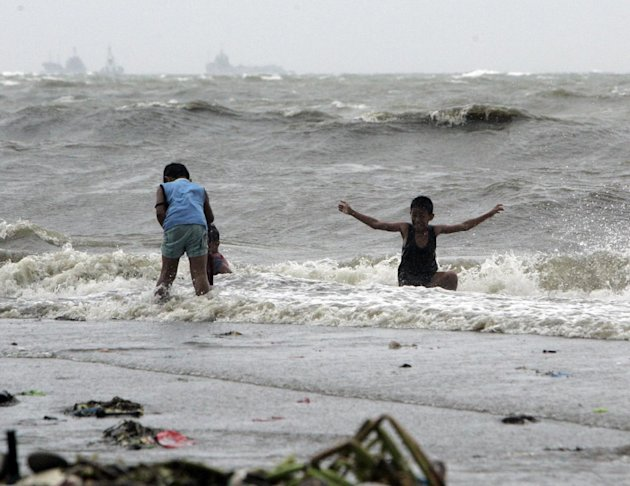 A boy enjoys the surf as another one looks for salvagable materials wash ashore due to Typhoon Nanmadol Saturday, Aug. 27, 2011 in Manila, Philippines. Forecasters said the typhoon hit the northeaster