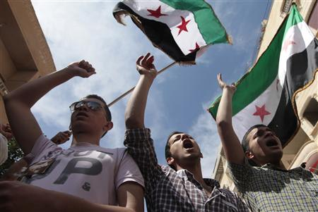 Demonstrators chant slogans and wave Syrian opposition flags during a protest against President Bashar al-Assad after Friday prayers in Raqqa province, east Syria