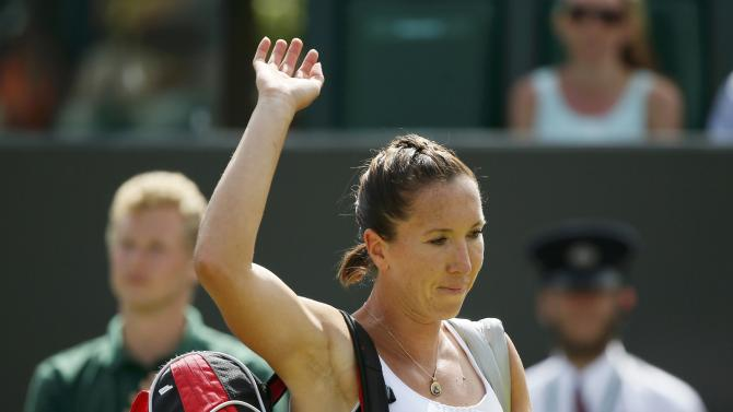 Jelena Jankovic of Serbia waves to fans after losing her match against Agnieszka Radwanska of Poland at the Wimbledon Tennis Championships in London