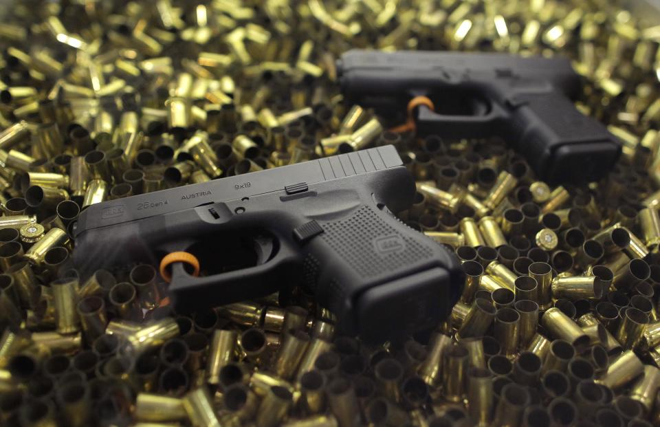 Two Glock 26 hand guns lay on a bed of empty shell casings while on display at the Shooting Hunting and Outdoor Trade show, Tuesday, Jan. 18, 2011 in Las Vegas. (AP Photo/Julie Jacobson)