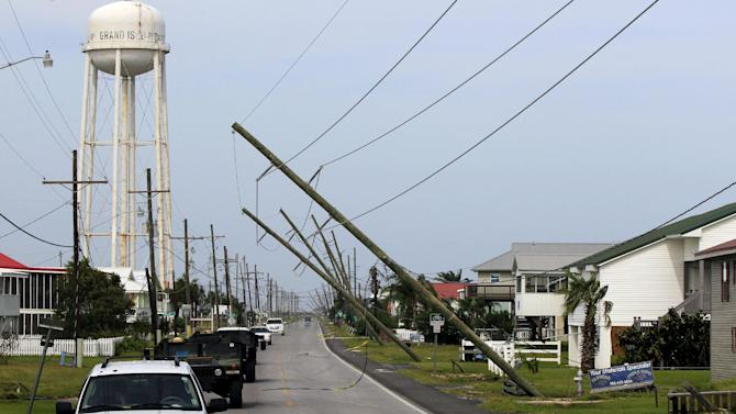 Utility poles are heavily damaged in the aftermath of Isaac as Louisiana Gov. Bobby Jindal's motorcade passes through Grad Isle, La., Friday, Aug. 31, 2012. Isaac is now a tropical depression, with the center on track to cross Arkansas on Friday and southern Missouri on Friday night, spreading rain through the regions. (AP Photo/Gerald Herbert)