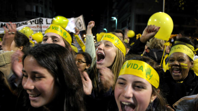 """People demonstrate against abortion legalization in downtown Montevideo, Uruguay, Monday, Sept. 24, 2012. Demonstrators protested the day before a congressional bill legalizing abortion is voted on. The headbands read in Spanish """"yes to life."""" (AP Photo/Matilde Campodonico)"""