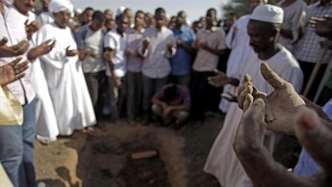 Sudanese men pray over the body of Salah Sanhory, 26, who was killed on Friday Sept. 27, 2013 by security forces, during his funeral in Khartoum, Sudan, Saturday, Sept. 28, 2013. The regime of President Omar al-Bashir is trying to stop public anger over fuel price hikes from turning into an Arab Spring-style uprising against his 24-year rule. But a crackdown by security forces appears to be fueling the unrest. (AP Photo/Khalil Hamra)