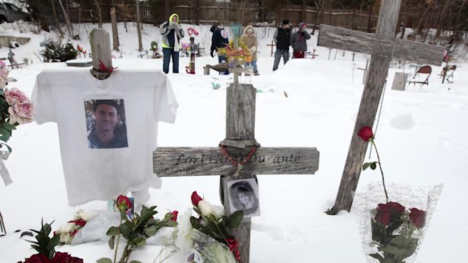 Mourners for those killed in The Station nightclub fire stand among makeshift memorials on the site of the fire, Sunday, Feb. 17, 2013, in West Warwick, R.I. The Station Fire Memorial Foundation unveiled final plans to build a permanent memorial at the site during ceremonies Sunday. The 2003 blaze, which broke out when pyrotechnics for the rock band Great White ignited flammable packing foam that had been installed inside the club as soundproofing, took the lives of 100 people. (AP Photo/Steven Senne)