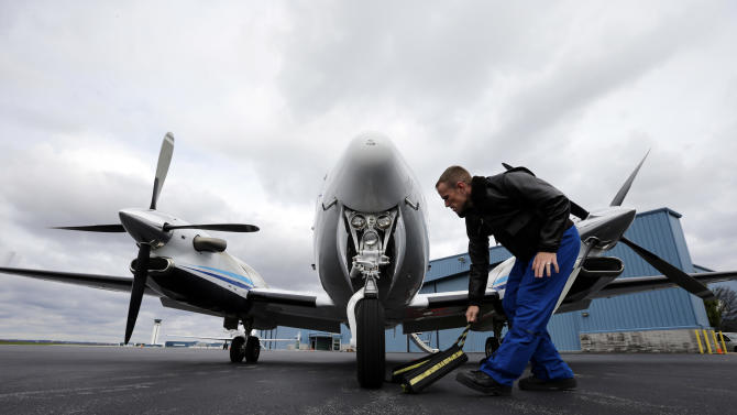 Pilot Lt. Com.  Scott Price removes the chocks before a National Oceanic and Atmospheric Administration flight to document coastal changes after Superstorm Sandy, Thursday, Nov. 1, 2012, in New Castle, Del. (AP Photo/Alex Brandon)