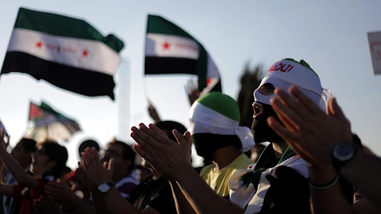 Masked Syrians with the revolutionary flag chant slogans against Bashar Assad, during a protest in front the Syrian embassy in Amman, Jordan, Thursday, June 28, 2012. (AP Photo/Mohammad Hannon)