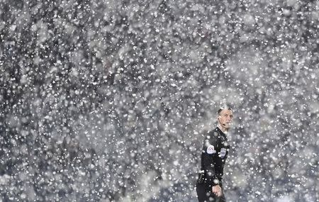 Referee Mark Clattenburg stands in the snow during the English Premier League soccer match between Manchester City and West Bromwich Albion at The Hawthorns in West Bromwich, central England