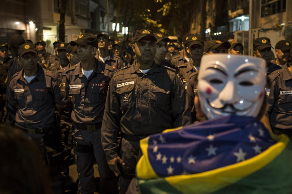 Police officers block a street during a protest outside the home of Sergio Cabral, the governor of Rio de Janeiro state, in Rio de Janeiro, Brazil, Sunday, June 23, 2013. A wave of protests have shaken Brazil and pushed the government to promise a crackdown on corruption and greater spending on social services. (AP Photo/Felipe Dana)