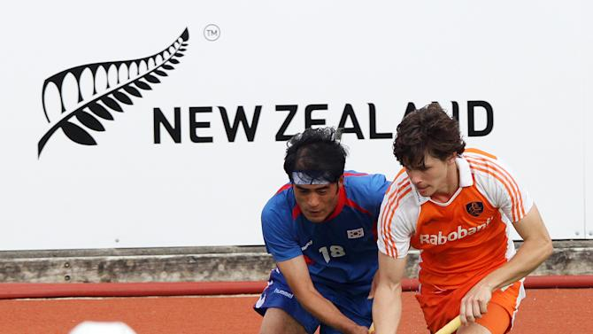 Wouter Jolie (R) of the Netherlands competes with Kim Young-Jin of South Korea (C) as the Netherlands goalkeeper Jacob Stockman (bottom) looks on during their first round match at the men's hockey Champions Trophy in Auckland on December 3, 2011. The Netherlands beat South Korea 2-0.   AFP PHOTO / Michael BRADLEY (Photo credit should read MICHAEL BRADLEY/AFP/Getty Images)