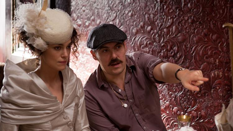 "FILE - This publicity film image released by Focus Features shows actress Keira Knightley, left, and director Joe Wright on the set of  the film, ""Anna Karenina."" While ""Pride & Prejudice"" and ""Atonement"" were fresh, lively takes for an age that finds costume drama stuffy, Wright planned a wild and possibly off-putting ride on ""Anna Karenina,"" confining most of the action to a dilapidated theater where the actors would perform in a stylized cinematic ballet without the usual grand sweep of period-drama locations. (AP Photo/Focus Features, Laurie Sparham, File)"