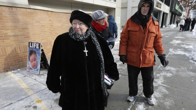 This photo taken Dec. 17, 2013 shows anti-abortion protester Eleanor McCullen, of Boston, left, standing at the painted edge of a buffer zone outside a Planned Parenthood location in Boston. With her pleasant demeanor and grandmotherly mien, McCullen has become the new face of a decades-old fight between abortion opponents asserting their right to try to change the minds of women seeking abortions and abortion providers claiming that patients should be able to enter their facilities without being impeded or harassed. William Cotter of Operation Rescue looks on at right. (AP Photo/Steven Senne)
