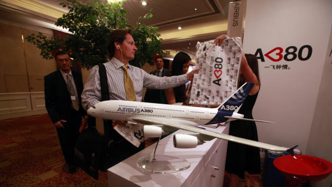 A visitor receives a gift bag near a model of the Airbus A380 passenger jet at the International Air Transport Association (IATA) 68th Annual General Meeting (AGM) and World Air Transport Summit held in Beijing, China, Monday, June 11, 2012. Squeezed by high oil prices, the world airline industry's profit will be slim this year and could be wiped out if Europe tumbles into recession, the global aviation trade group said Monday. (AP Photo/Ng Han Guan)