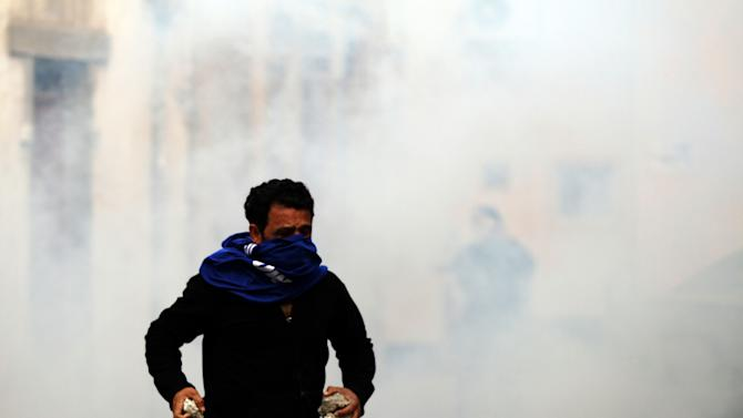 A masked Bahraini anti-government protester holding rocks runs through tear gas fired by riot police during clashes in Sanabis, Bahrain, Monday, Feb. 11, 2013. After nearly two years of nonstop unrest, opposing factions in Bahrain began talks on Sunday to ease an Arab Spring conflict that has run longer than Syria's rebellion and is playing out on the doorstep of the U.S. military's main naval base in the Persian Gulf. (AP Photo/Hasan Jamali)