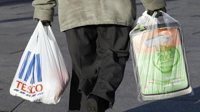 A woman carries shopping bags from Tesco and Asda in Long Eaton