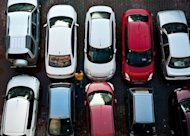 A pedestrian walks past cars at a parking lot in New Delhi. The shift toward vehicle ownership in the country of 1.2 billion people has reached a tipping point, driven by increasingly urban, affluent and aspirational first-time buyers in India, according to research firm LMC Automotive