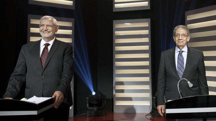 Moderate Islamist, Abdel-Moneim Abolfotoh, left, and former foreign minister, Amr Moussa stand at their podiums on Egypt's first televised presidential debate in Cairo, Egypt, Friday, May 11, 2012. Two presidential election front-runners, have squared off in the Arab world's first ever presidential debate, trading barbs over the role of religion and how to bring democratic reform to Egypt. (AP Photo/Mahmoud Khaled, Al Masry Al Youm)