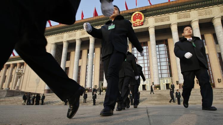 PLA soldiers in plain clothes march in front of the Great Hall of the People prior to a plenary session of the National People's Congress in Beijing
