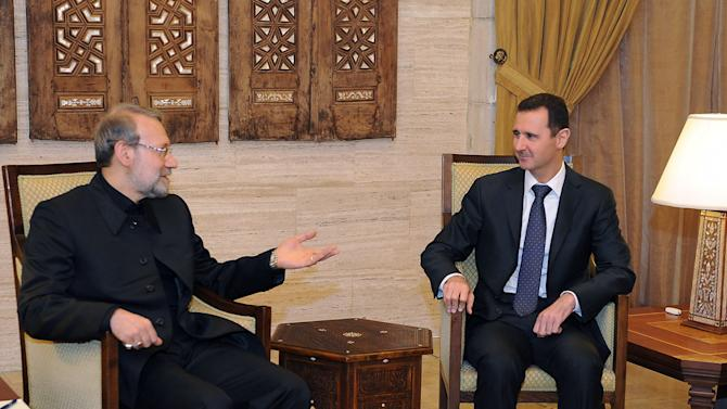 In this photo released by the Syrian official news agency SANA, Syria President Bashar Assad, right, meets with the speaker of the Iranian parliament, Ali Larijani, left, in Damascus, Syria, Friday Nov. 23,  2012. Larijani was in Damascus where he held talks Friday with Assad and other officials before flying on to neighboring Lebanon. (AP Photo/SANA)