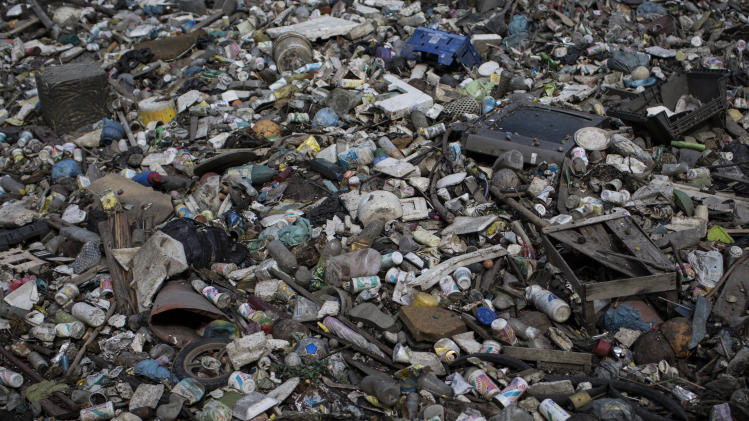 FILE - In this May 15, 2014 FILE photo, trash floats on a polluted water channel that flows into Guanabara Bay in Rio de Janeiro, Brazil. Rio de Janeiro Mayor Eduardo Paes said Saturday, June 7, 2014 that the city will fail to keep the promise of cleaning polluted Guanabara Bay for the 2016 Olympics, which it made five years ago when it was awarded the games. (AP Photo/Felipe Dana, FILE)