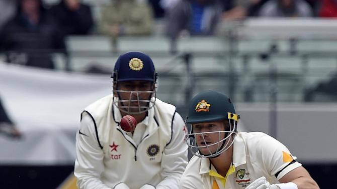 India's MS Dhoni, left, watches on as Australia's Shane Watson bats during their play on day one of the third cricket test in Melbourne, Australia, Friday, Dec. 26, 2014. (AP Photo/Andy Brownbill)