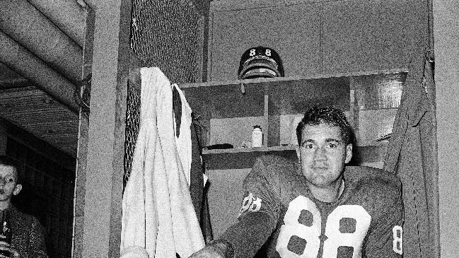 FILE - In this Nov. 8, 1959, file photo, New York Giants place kicker Pat Summerall shows off kicking shoe for photographers in the locker room after making three field goals to help the team to a 9-3 win over the Chicago Cardinals at Yankee Stadium in New York. Fox Sports spokesman Dan Bell said Tuesday, April 16, 2013, that Summerall, the NFL player-turned-broadcaster whose deep, resonant voice called games for more than 40 years, has died at the age of 82. (AP Photo/John Lindsay, File)