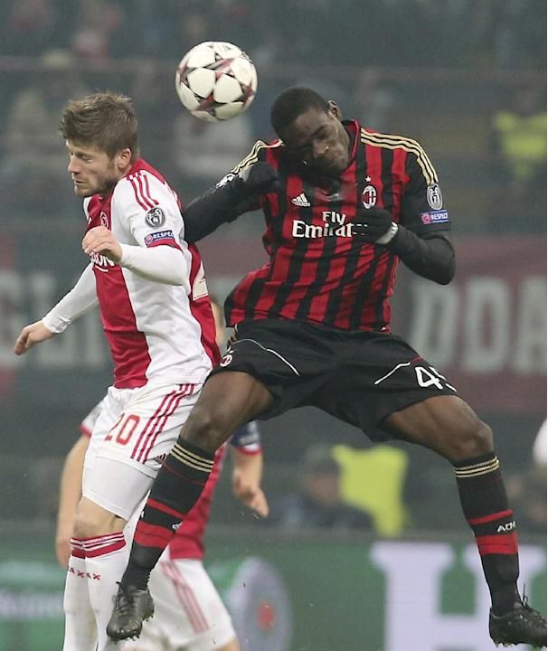 Ajax midfielder Lasse Schone, left, of Denmark, jumps for the ball with AC Milan forward Mario Balotelli during a Champions League, Group H, soccer match between AC Milan and Ajax at the San Siro stad