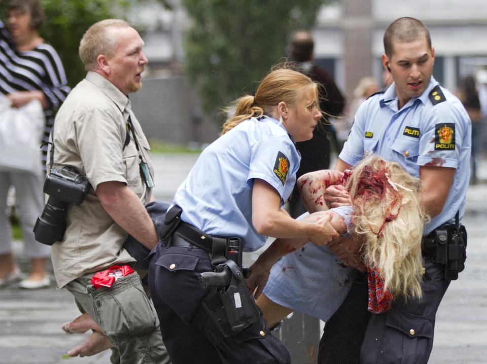 A young victim is helped in the center of Oslo, Friday July 22, 2011, following an explosion that tore open several buildings including the prime minister's office, shattering windows and covering the street with documents. (AP Photo/Scanpix, Winje Ãjijord) NORWAY OUT