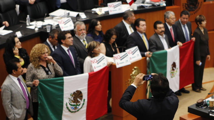 An assistant to the Senate takes photographs of senators of the PRD holding national flags while interrupting a debate on an energy reform bill at the Senate in Mexico City