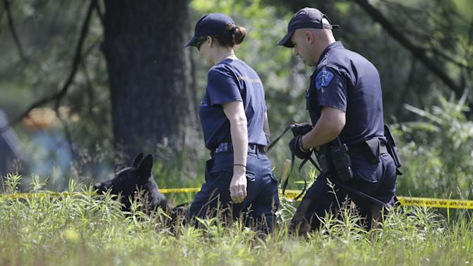 Law enforcement officials from the Michigan State Police help search the area in Oakland Township, Mich., Tuesday, June 18, 2013 where officials continue the search for the remains of Teamsters union president Jimmy Hoffa who disappeared from a Detroit-area restaurant in 1975. (AP Photo/Carlos Osorio)