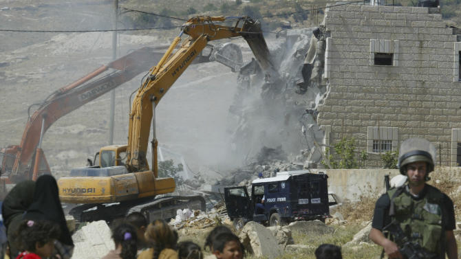 FILE- In this file photo taken on June 2, 2004, Palestinians look as the Israeli authorities demolish a house that was built without the proper permits, according to Israel, in the West Bank village of Anata near Jerusalem. An Israeli defense official says, Tuesday, Sept. 6, 2011, the military is temporarily suspending its contentious policy of demolishing illegally built Palestinian homes in the West Bank after determining the policy is not equally enforced against illegally built Jewish settler homes. (AP Photo/Oded Balilty, File)