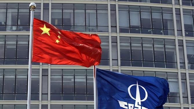 A COSCO company flag and a Chinese national flag fly in front of the company's headquarters in Beijing