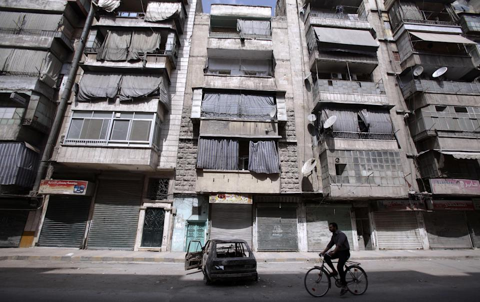 A Syrian man rides his bicycle by apartments abandoned due to government shelling, in Aleppo, Syria, Tuesday, Sept. 11, 2012. (AP Photo/Muhammed Muheisen)