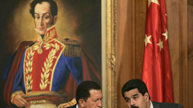 """FILE .- In this Oct. 17, 2006 file photo Venezuelan President Hugo Chavez, left, talks with his then Foreign Minister and current Vice-President Nicolas Maduro during a meeting with Chinese businessmen at Miraflores Palace in Caracas, Venezuela.  Chavez is to return to Cuba Sunday for another surgery in his battle against cancer, which has led him to speak publicly of a successor for the first time.  Chavez said Saturday that if there are """"circumstances that prevent me from exercising the presidency further""""  Vice-President Nicolas Maduro should replace him for the remainder of his term. (AP Photo/Fernando Llano, File)"""