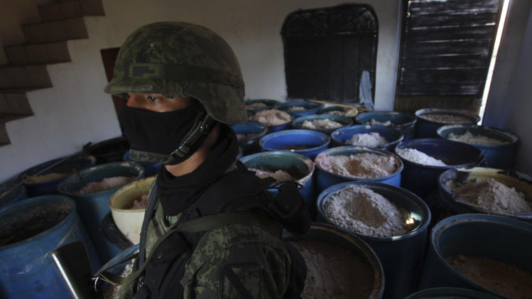 """FILE - In this Feb. 9, 2012, file photo a soldier stands in a room full of barrels containing white and yellow powder after a seizure of 15 tons of pure methamphetamine at a small ranch in Tlajomulco de Zuniga, on the outskirts of Guadalajara, Mexico. Mexican drug cartels are flooding U.S. cities with cheap, extraordinarily pure methamphetamine made in factory-like """"super labs"""" _ a surge in production that has all but negated the nation's long effort to curb meth production at home with tighter controls on key ingredients.  (AP Photo/Bruno Gonzalez, File)"""