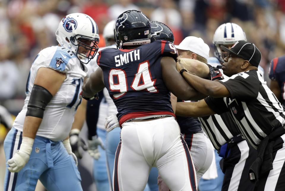 Officials break up a skirmish between players including Tennessee Titans' David Stewart, left, and Houston Texans' Antonio Smith (94) in the second quarter of an NFL football game Sunday, Sept. 30, 2012, in Houston. (AP Photo/Eric Gay)