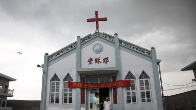 """In this photo taken July 15, 2014, Pastor Tao Chongyin, left, speaks with church member Fan Liang'an in front of the Wuxi Christian Church with the words """"Church of Jesus"""" in red, in Longwan, Wenzhou in eastern China's Zhejiang province. When one rural village re-erected a cross in the summer, authorities put it under a 24-hour watch, which has now gone on for nearly five months. """"This year's Christmas has been exceptional, as a group of uniformed men have been helping us move tables, direct traffic, and guard holiday decorations as well as the front door, the back door, the warehouse and the sanctuary,"""" Tao wrote on a social media site. (AP Photo/Didi Tang)"""