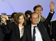 France&#39;s Socialist Party (PS) newly elected president Francois Hollande and his companion Valerie Trierweiler wave on stage at the Place de la Bastille after the announcement of the first official results of the French presidential second round