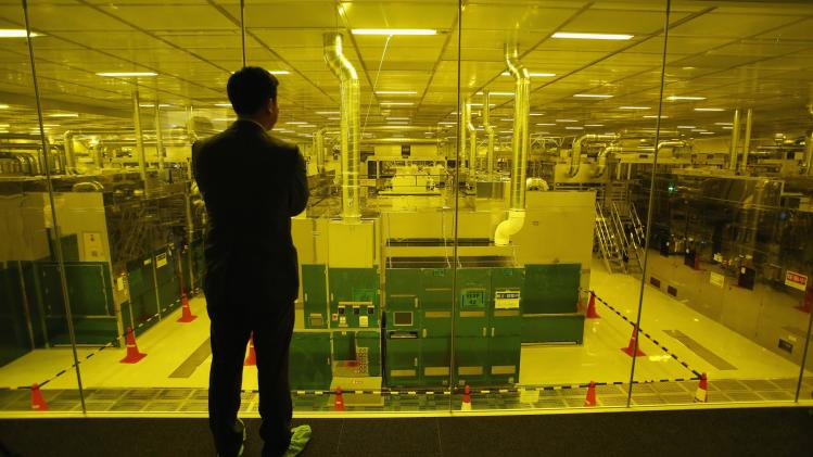 File photo of journalist looking through glass wall at Japan Display Inc's new production line for LCD panels in its factory in Mobara
