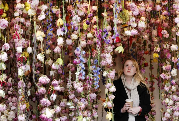 A woman walks through floral artist Rebecca Louise Law's stand at the Chelsea Flower Show in London