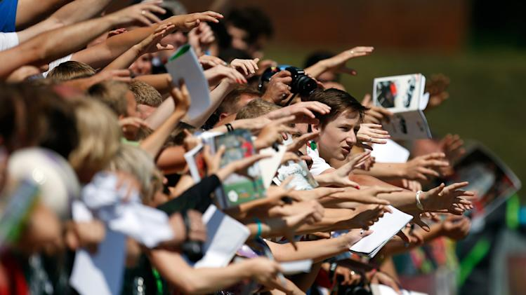 Fans try to get the attention of Potyugal players during a training session of Portugal, prior to their Euro 2012 soccer semifinal match, in Opalenica, Poland, Saturday, June 23, 2012. (AP Photo/Armando Franca)