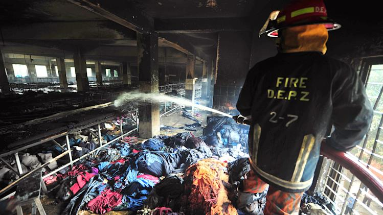 A Bangladeshi firefighter douses the inside of a garment factory outside Dhaka, Bangladesh, Sunday, Nov. 25, 2012. At least 112 people were killed in a late Saturday night fire that raced through the multi-story garment factory just outside of Bangladesh's capital, an official said Sunday. (AP Photo/ khurshed Rinku)