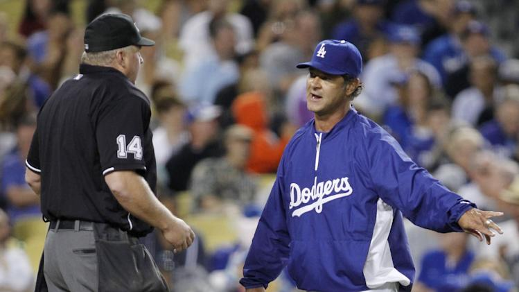 Los Angeles Dodgers manager Don Mattingly, right, argues talks with home plate umpire Bill Miller after Dodgers' Mark Ellis was tagged out on the third base line during the fourth inning of a baseball game against the Philadelphia Phillies on Monday, July 16, 2012, in Los Angeles. (AP Photo/Danny Moloshok)