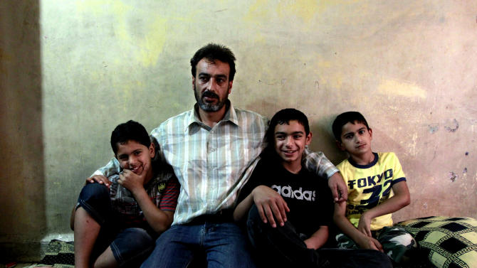 In this Friday, May. 24, 2013 photo, Syrian Abu Mohammed, who fled his home from Homs 18 months ago, sits with his three sons, as he speaks during an interview with The Associated Press, in the northern port city of Tripoli, Lebanon. Fighting between Bab Tabbaneh and Jabal Mohsen, which goes back to Lebanon's civil war, has become more frequent since the start of the Syrian conflict in 2011, with the neighborhoods backing opposite sides. And the latest round over the past week has been the longest yet and has left tens dead and hundreds wounded, the highest toll so far. (AP Photo/Bilal Hussein)