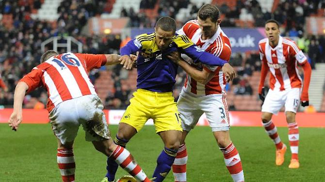 Swansea's Wayne Routledge is held back by Stoke's Erik Pieters, right, and  Charlie Ad during the English Premier League soccer match between Stoke City and Swansea City at Britannia Stadium in Stoke on Trent, England, Wednesday, Feb. 12, 2014