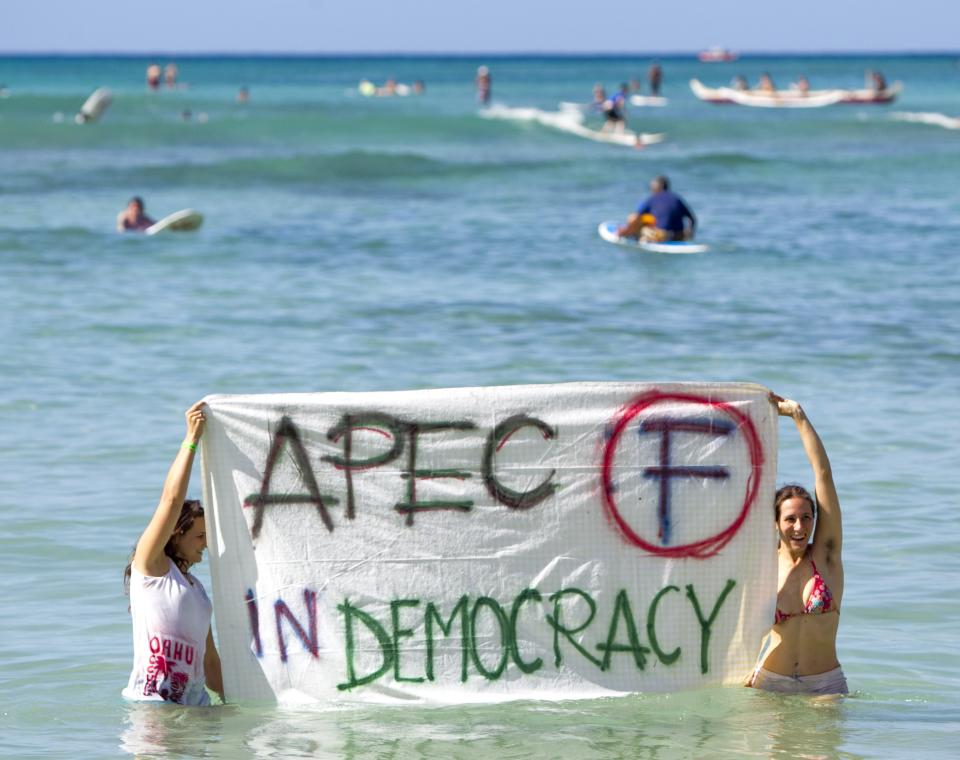 Two protesters stand in the water holding anti-APEC signs at Waikiki Beach in Honolulu on Saturday, Nov. 12, 2011 as the summit is held in Oahu over the weekend. (AP Photo/ Marco Garcia)