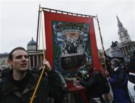 A man carries a banner representing the National Union of Mineworkers through the crowd at a party to celebrate the death of the late former British prime minister Margaret Thatcher in central London April 13, 2013. REUTERS/Olivia Harris